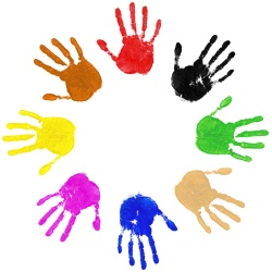 Multi coloured painted handprints arranged in a circle on white